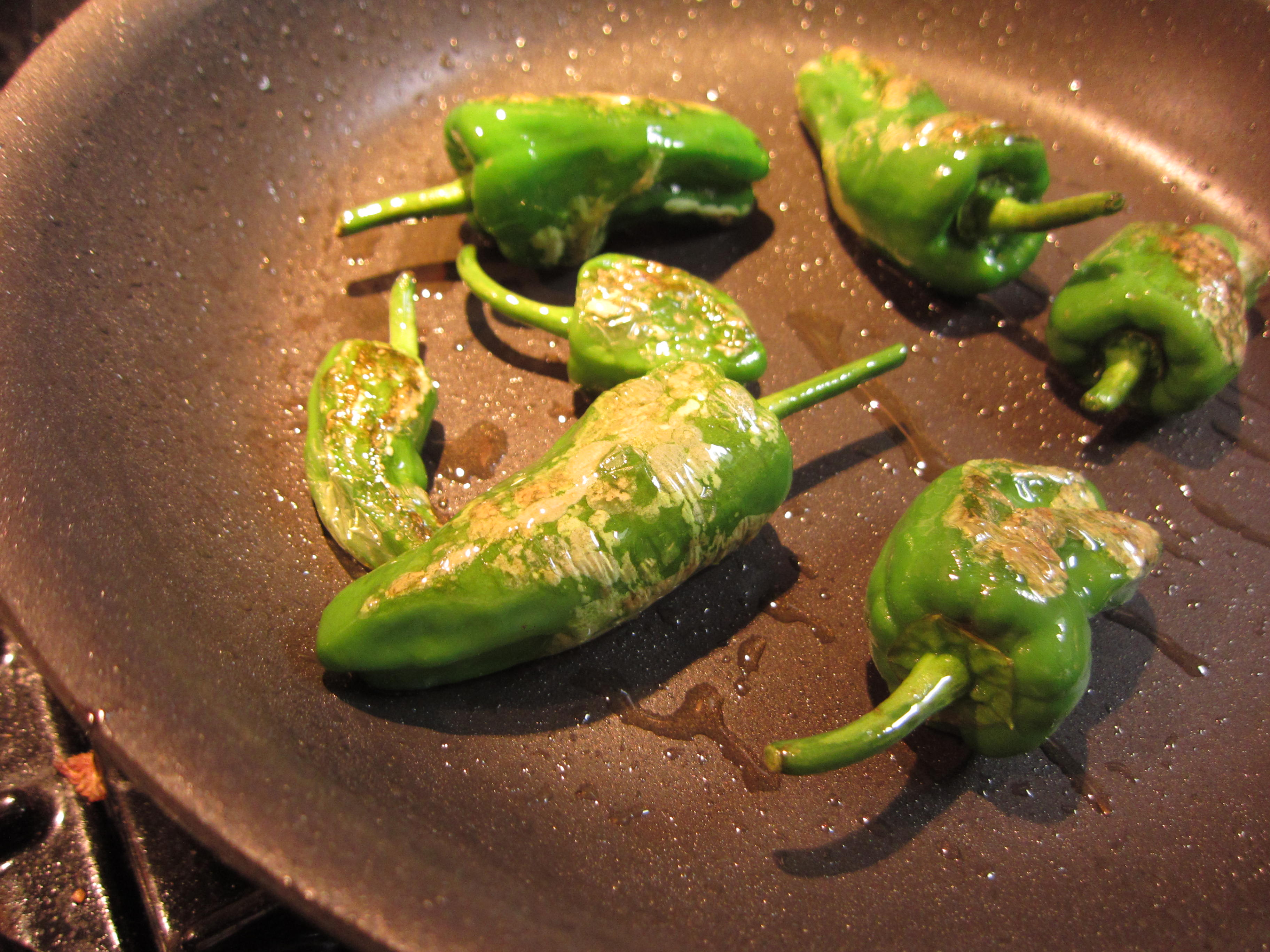 Blistered Padrón peppers in hot oil. It only takes a few minutes.