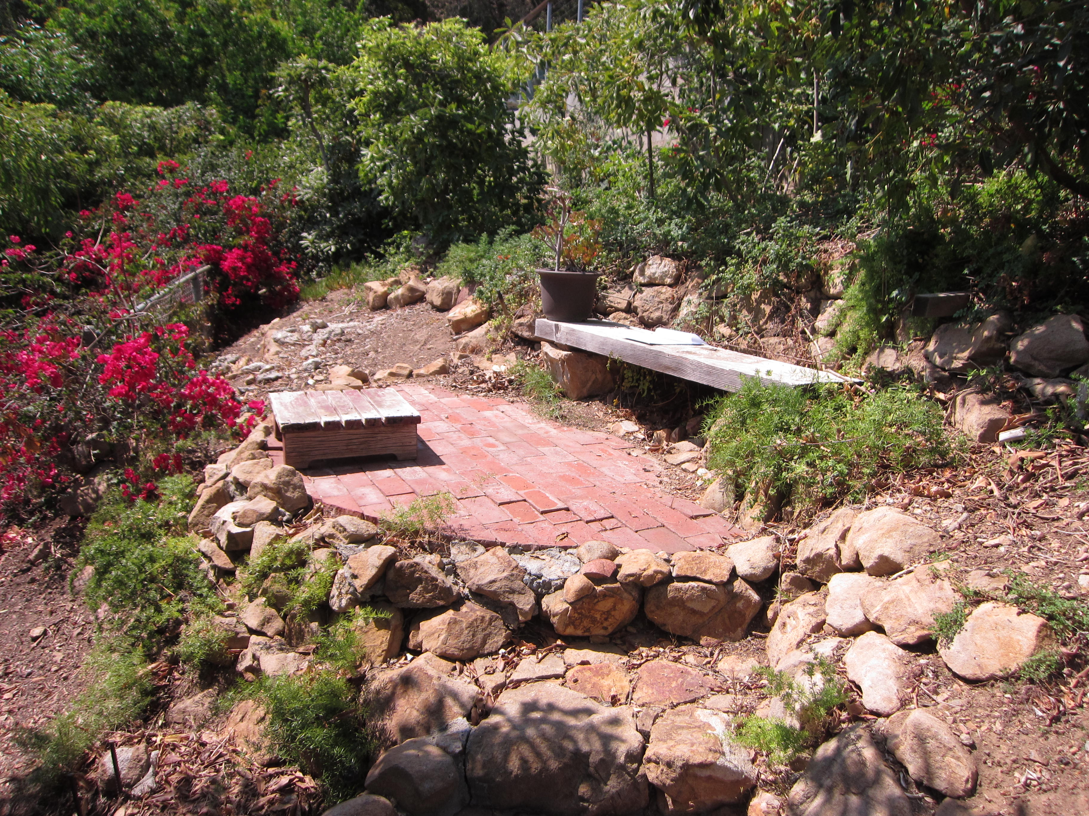 A tiny patio tucked into the hillside is our location for a starter garden.
