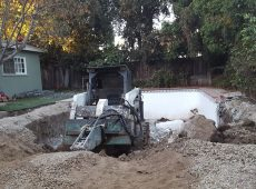 Bulldozer at work demolishing the client's swimming pool.