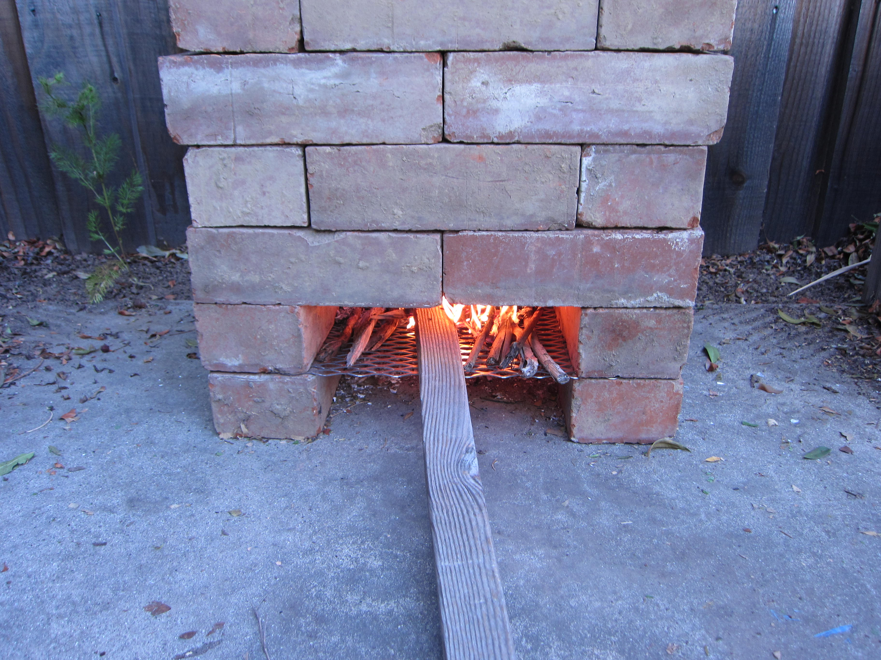 Once the coals catch fire, we started feeding in larger pieces of wood.